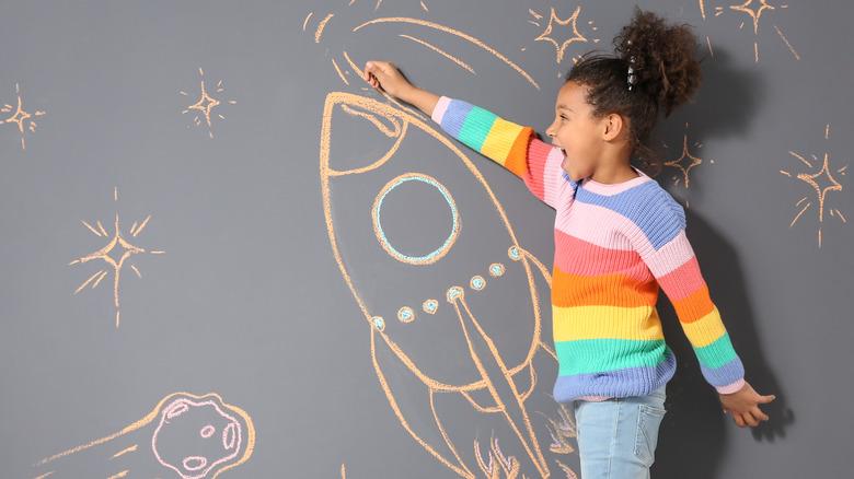 Child drawing on chalkboard wall