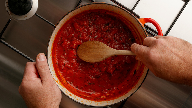 stirring sauce with wooden spoon