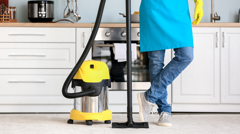 person with vacuum in kitchen