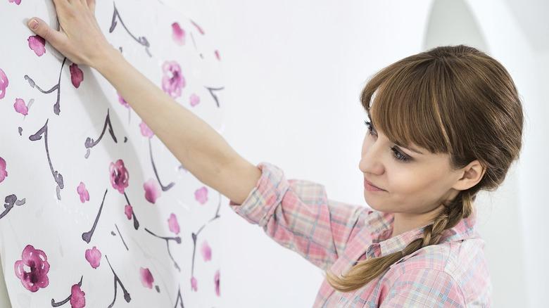 woman applying wallpaper