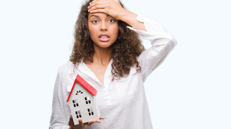 stressed woman holding small house