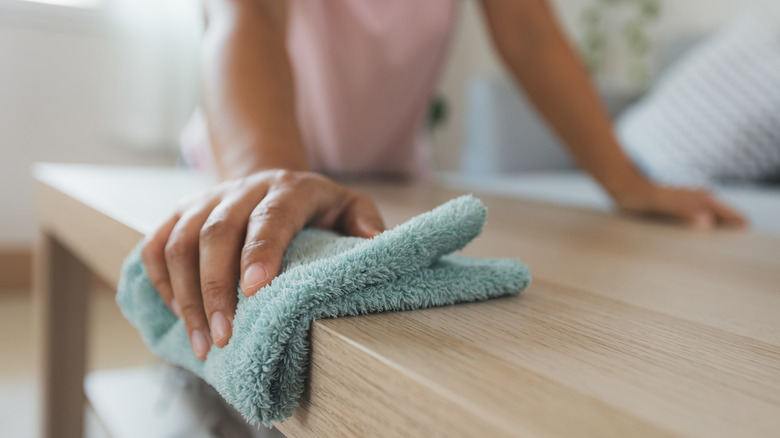 A hand dusting furniture