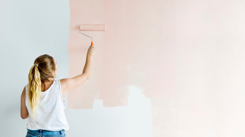 woman painting pink wall