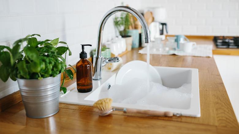white dish soaking in sudsy sink