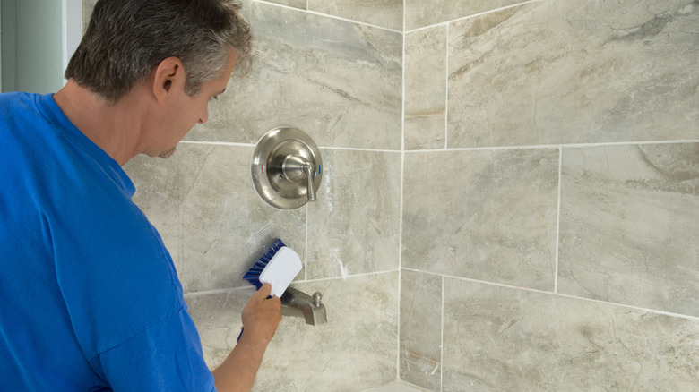 Man cleaning the grout in the shower