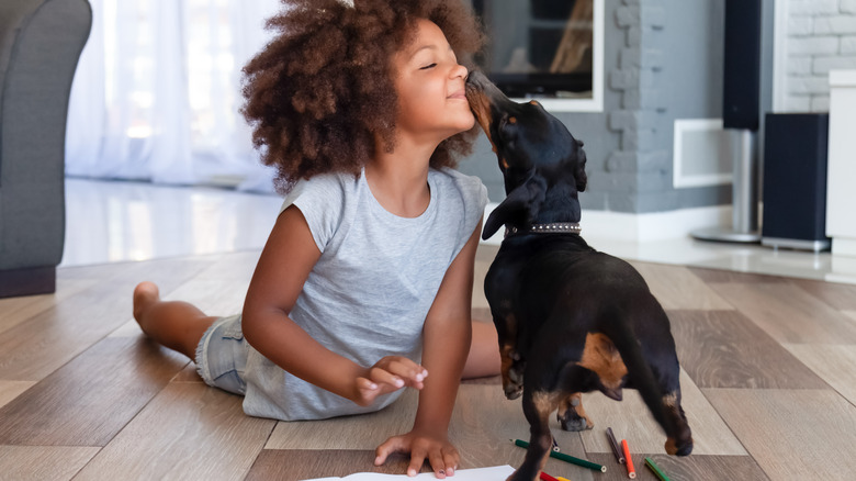 A girl and a dog on a floor