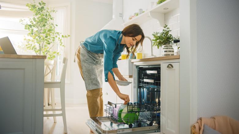 maid loading dishwasher