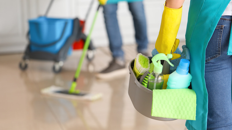 Couple with cleaning supplies