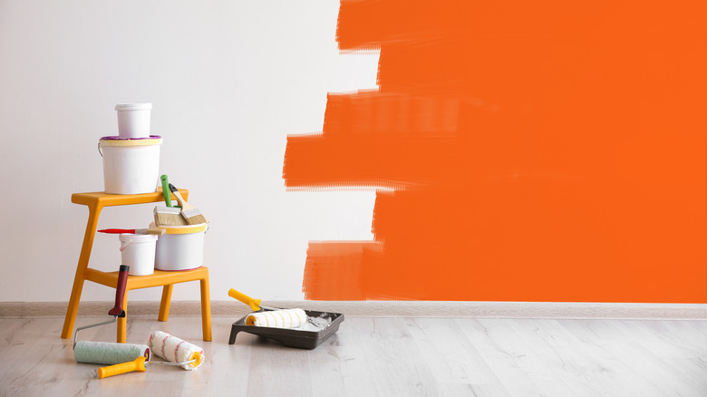 Painting supplies and orange and white wall