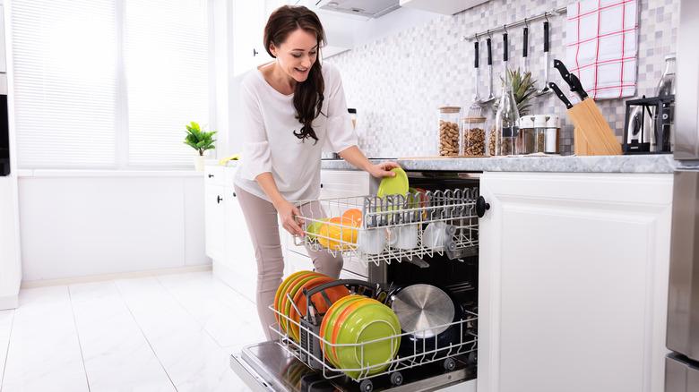 Woman loading top dishwasher tray