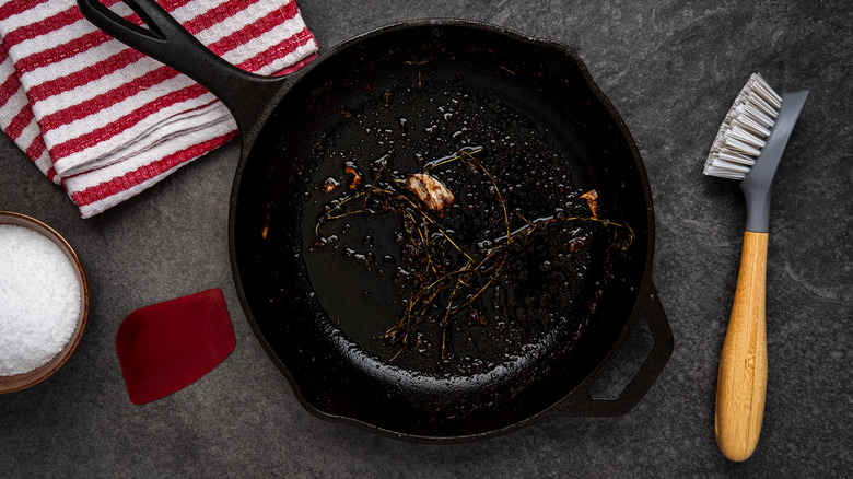 Dirty cast-iron pan with salt and a kitchen towel