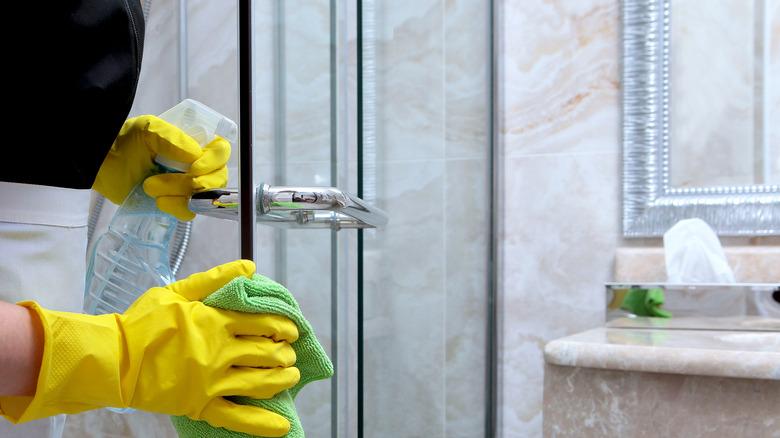 woman cleaning glass shower door