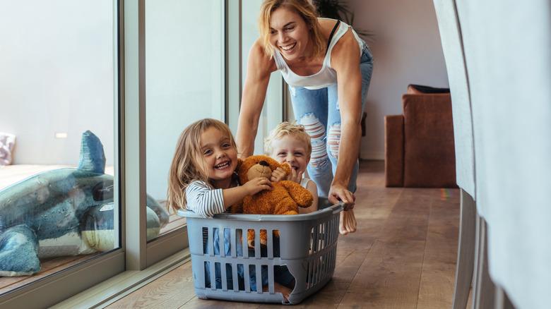 mom pushing kids in laundry basket