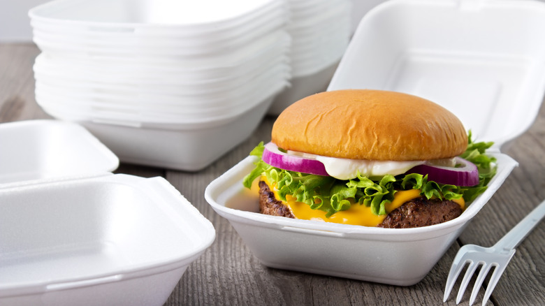styrofoam containers with one holding a burger