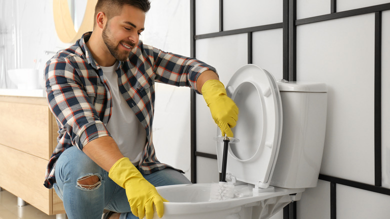 Man smiling while cleaning toilet