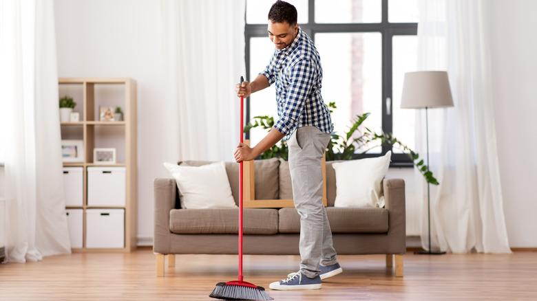 man sweeping wood floors