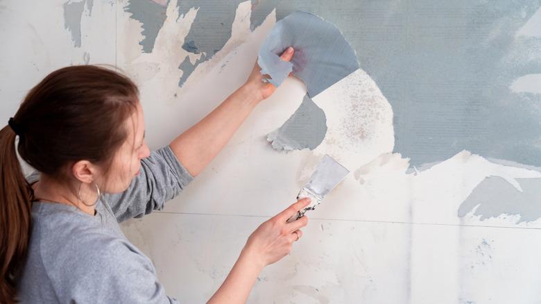 brunette woman removes blue wallpaper