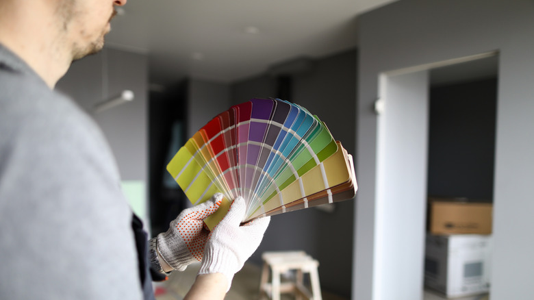A man holding paint swatches