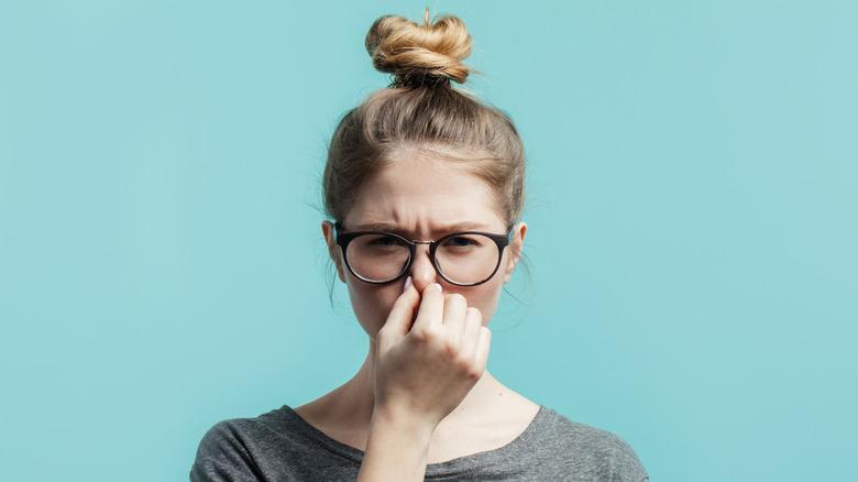 Girl smelling odor