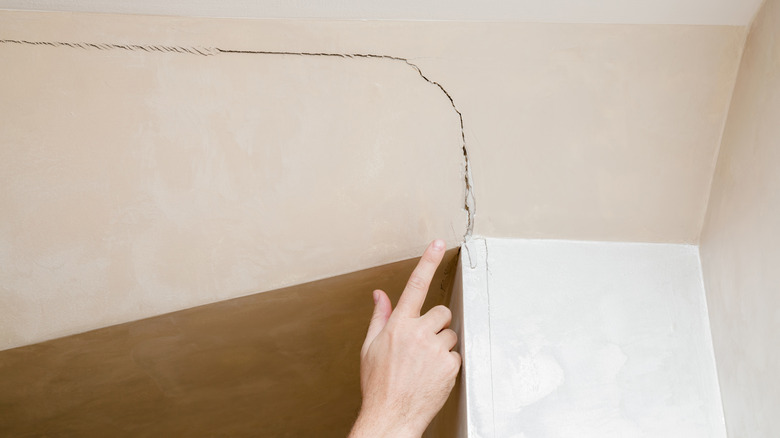 someone pointing at cracked wall