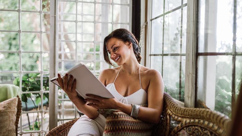 woman reading in sunroom