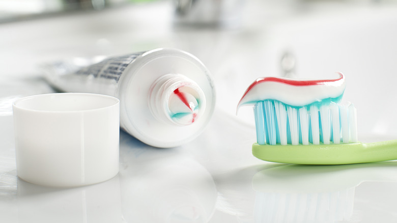 toothpaste in bottle and on toothbrush
