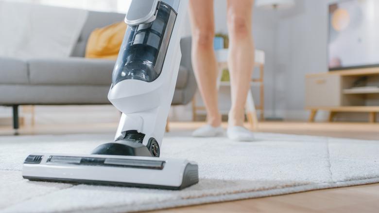 Person vacuuming rug
