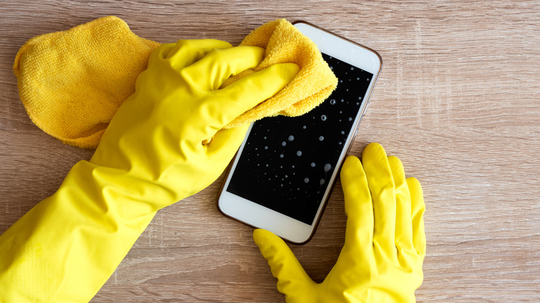 Gloved hands wiping cell phone